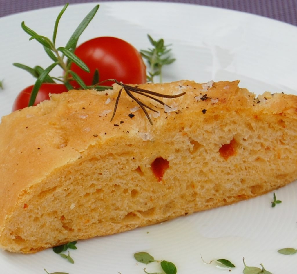 herbed, sun-dried tomato focaccia slice with tomatoes